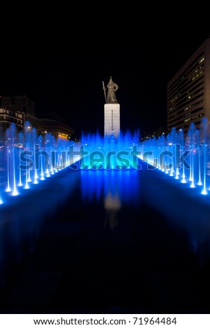 A beautifully colored blue water fountain illuminates the front of the centered historic Admiral Yi Sun Sin statue at night in downtown Seoul, South Korea. Vertical copy space