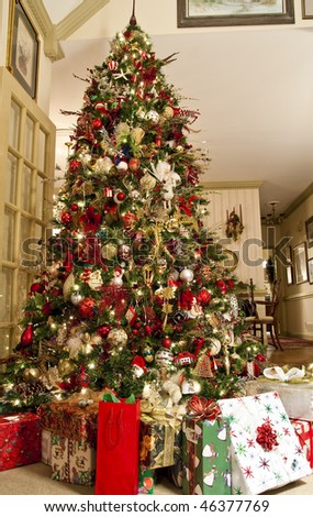 A beautifully decorated tree with presents in a nice home