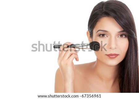 a beauty portrait of a younf woman, applying blush on her cheecks with a blusher brush