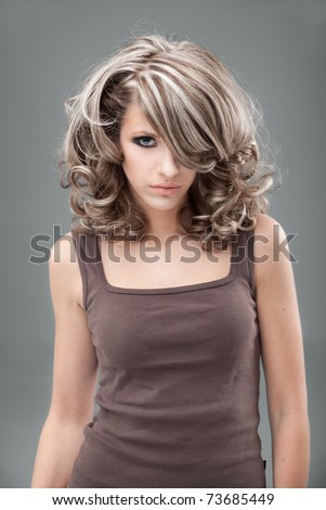 a beauty portrait of a young, blonde woman, wearing a 1960's make-up and hairstyle and a brown top. - stock photo