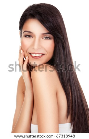 a beauty portrait of a young woman, shot on white background. she has long, dark brown hair; she looks over her shoulder smiling, while she is touching her face with her hand.