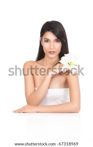 a beauty portrait of a young woman, shot on white background. she has long, dark brown hair; she rests one arm on a white table and with the other one is holding a lily next to her shoulder. - stock photo
