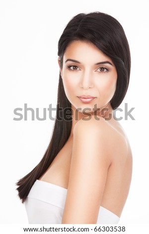 a beauty portrait of a young woman, shot on white background. she looks over her shoulder, straight to the camera. - stock photo