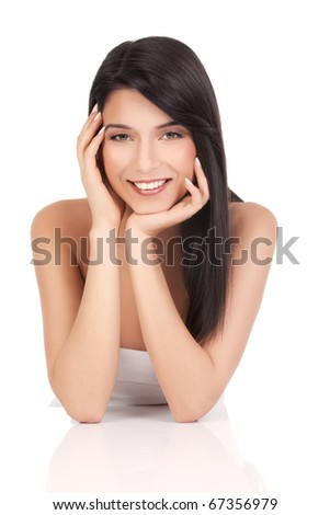 a beauty portrait of a young woman, smiling, shot on white background.  she rests her elbows on a white table and touches her face delicately with her fingers