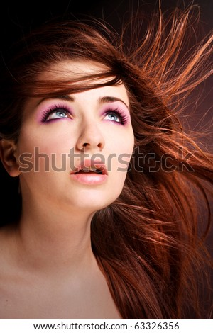 A beauty shot of a young blue eyed woman with her hair flowing in the wind looking to the heavens. - stock photo