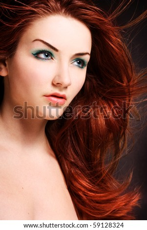 A beauty shot of a young blue eyed woman with her red hair flowing in the wind. - stock photo
