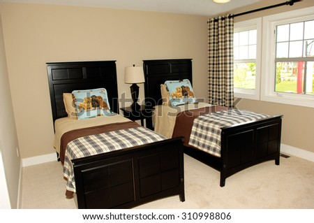 A bedroom in a new house with two single beds and large window's. - stock photo