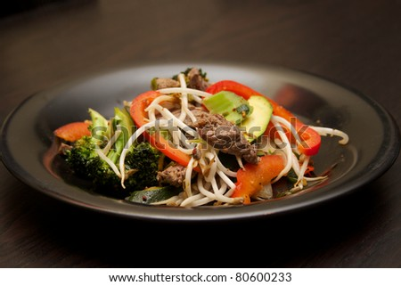 A Beef Stir fry on a black plate