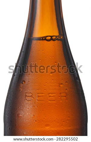 A beer bottle on a white background with condensation.