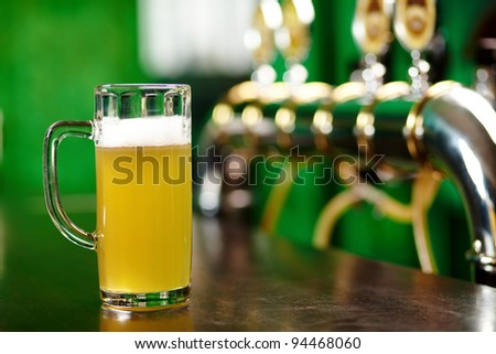 A beer pint standing on a bar counter not far from beer taps - stock photo