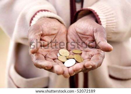 A beggar holding out his hands filled with coins. - stock photo
