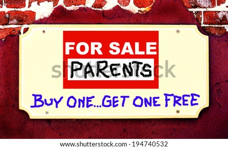 "A Beige Placard Sign On Maroon Stucco And Brick Background With A Sign Saying ""FOR SALE, PARENTS, BUY ONE GET ONE FREE""."