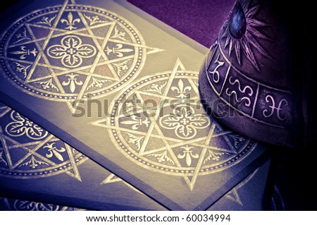 a bell with astrological symbols over tarots cards - stock photo