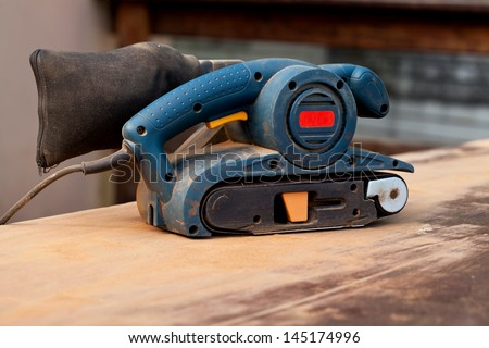 A belt sander tool on a wooden surface with saw dust - stock photo