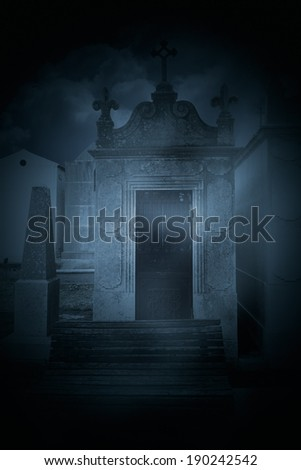 A bench in an old dark cemetery - stock photo