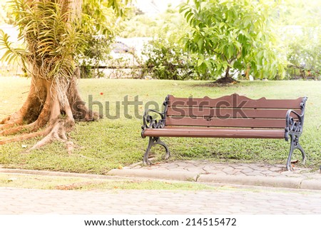 A bench in the alley in the park on a sunny day - stock photo