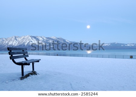 A bench on moonlit Regan beach at Lake Tahoe, California. The moon shines in the sky, lighting Sierra Nevada mountains.