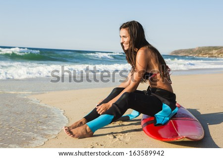 A beuatiful surfer girl making preparation for a surf session - stock photo