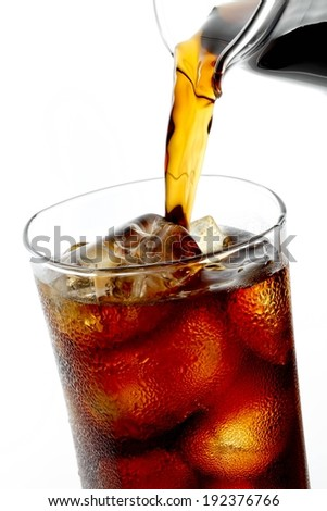 A beverage being poured into a glass full of ice. - stock photo
