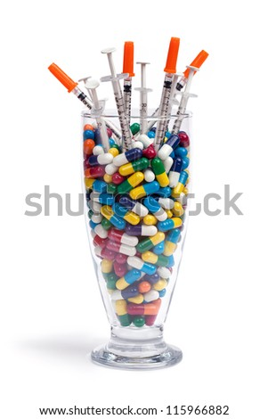 A beverage glass filled with pills and syringes isolated on white. - stock photo