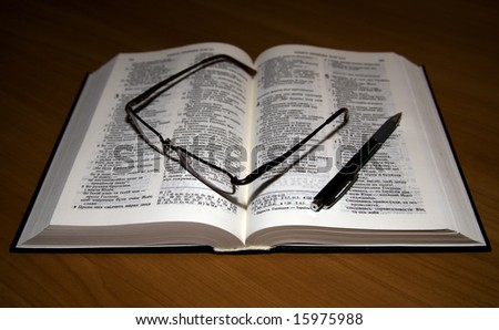 A bible is on a table, glasses, pen. Religious theme, Bible.