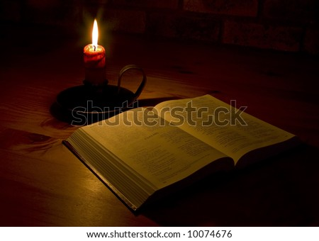 A bible open on a table next to a candle. The light illuminating the bible is only from the candle. Perfect for religion, easter and christmas themes. - stock photo