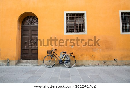 A bicycle leaning against an old plaster wall in Tuscany - stock photo