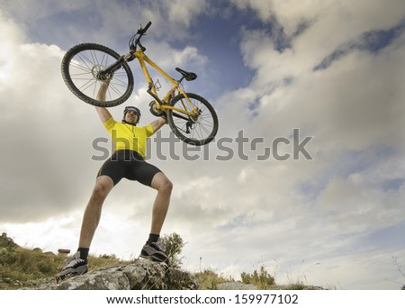 A bicycle rider raises a dramatic sky. Effort or victory symbol. - stock photo