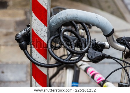 a bicycle was taken firmly to prevent the theft of a rod. bike lock anti-theft lock - stock photo
