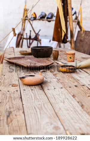 a big and old wooden table with some medieval items on it - stock photo
