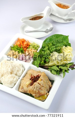 A big assortment of Thai foods and appetizers presented beautifully with fancy garnish. - stock photo