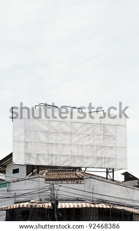 A big blank grungy metallic advertisement billboard on the rooftop of an old aging vintage shop house against a clear blue sky, with space for text. - stock photo
