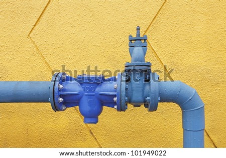 A big blue color water supply main pipeline with a stopcock valve against a yellow concrete wall. - stock photo
