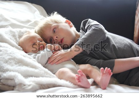 A big brother is lovingly hugging his newborn baby sister as they lay in bed together. - stock photo