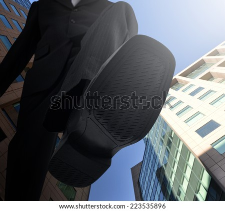 A big business man's shoe is stepping down with a city of buildings in the background for a employment or employee concept. - stock photo