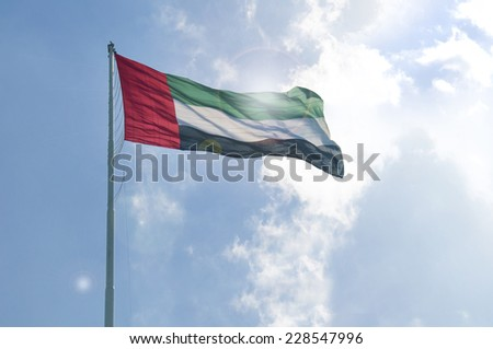 A big flag of UAE flying high in the sky. UAE celebrates National Day on 2nd December every year. - stock photo