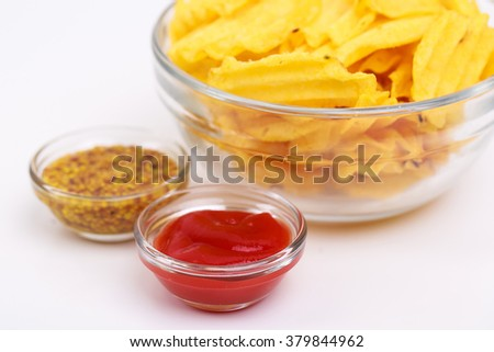a big glass bowl with crispy potato chips, a tomato ketchup in a small glass bowl, a mustard in a small glass bowl, isolated - stock photo