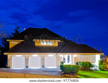 A big luxury house with triple garage in suburbs at dusk ( night ) in Vancouver, Canada