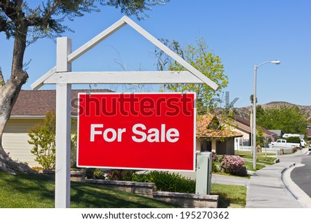 A big red sale sign hangs in the front yard of a house in a suburban community.  - stock photo
