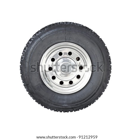a big rubber tire mounted on a chrome plated wheel hub of a truck isolated