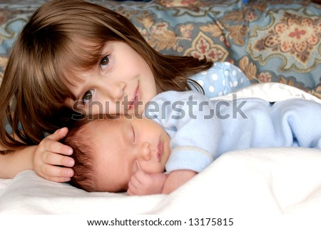 A big sister giving her baby brother some love - stock photo