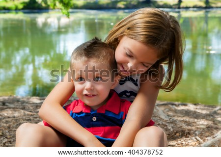 A big sister sits with her little brother in her lap while she hugs him.  She leans over and in adoration, she looks down at him. - stock photo
