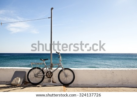 A bike against a white wall at the sea on Samos island, Greece - stock photo
