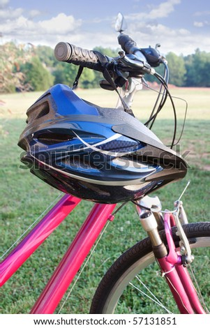 A bike helmet hangs from the handlebars of a bicycle.