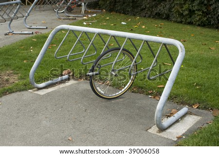 A bike rack with a wheel locked to it - stock photo