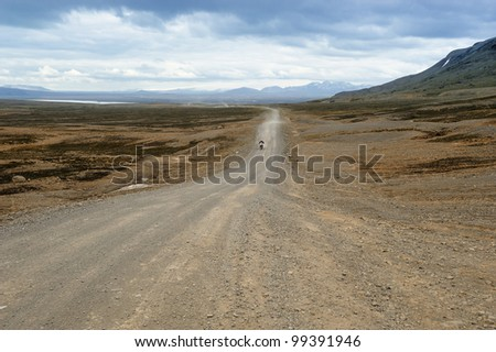 a biker traveling on a dirt road of Iceland - stock photo
