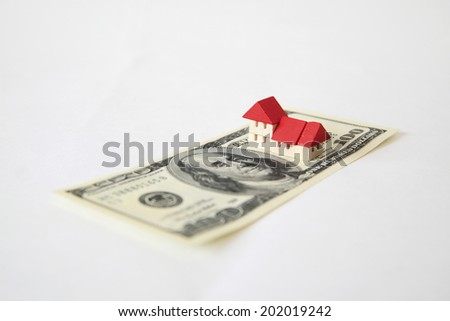 A $100 Bill And A Toy House