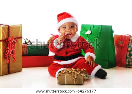 A biracial baby Santa happily chewing on a candy cane among wrapped Christmas gifts.  Isolated on white. - stock photo