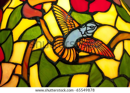 A bird in stained glass of  lamp. - stock photo