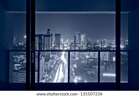A bird's eye view of the city night view outside the window - stock photo